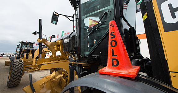 A Caterpillar motor grader is sold at a Ritchie Bros. equipment auction.